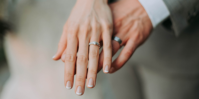 Photo of a bride and groom's hands with wedding rings